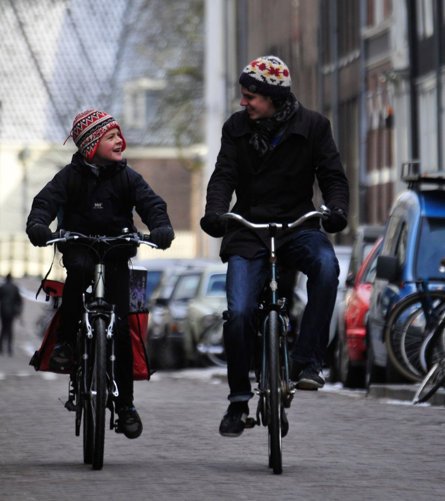 Man and child riding bicycles side by side, engaged in conversation